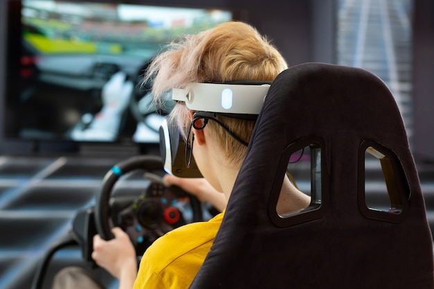 ハンドルを握り、コンソールでコンピューター ゲームをする、仮想現実の眼鏡をかけた 10 代の少年