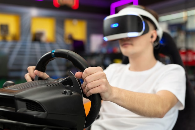 Teenage boy wearing virtual reality glasses, who holds on to the steering wheel and plays a computer game on the console