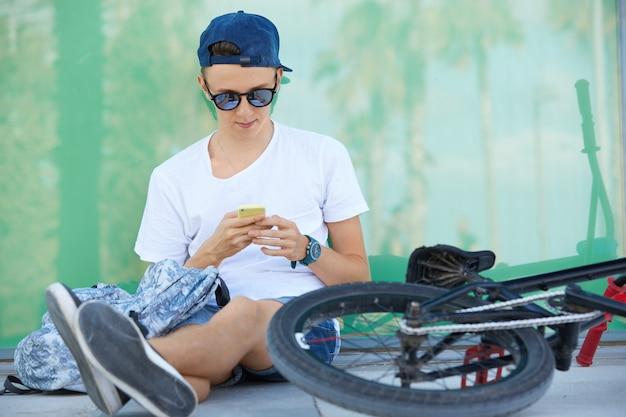 Ragazzo adolescente che indossa la maglietta bianca e utilizza lo smartphone