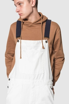 Ragazzo adolescente in salopette bianca e felpa marrone streetwear servizio fotografico
