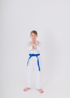 Teenage boy in a white kimono with a blue belt stands in a pose on a white wall