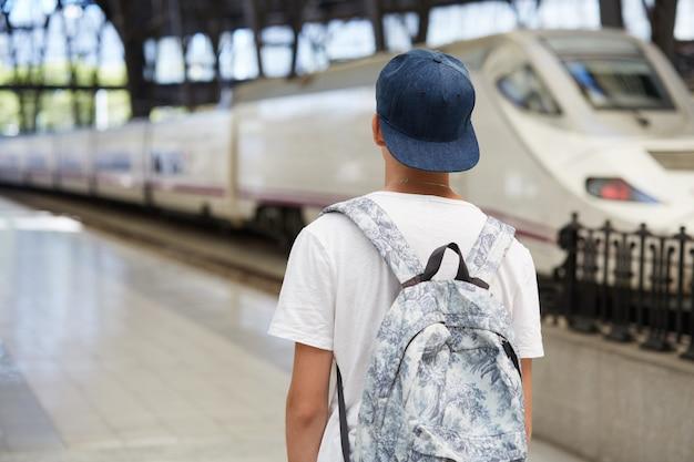 Подросток с рюкзаком и кепкой