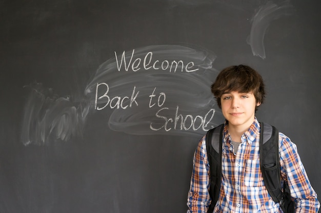 Teenage boy with backpack and back to school written with chalk on black board