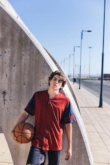 カメラを見てバスケットボールの十代の少年