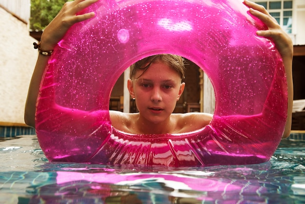 Teenage boy with buoy swimming in the pool