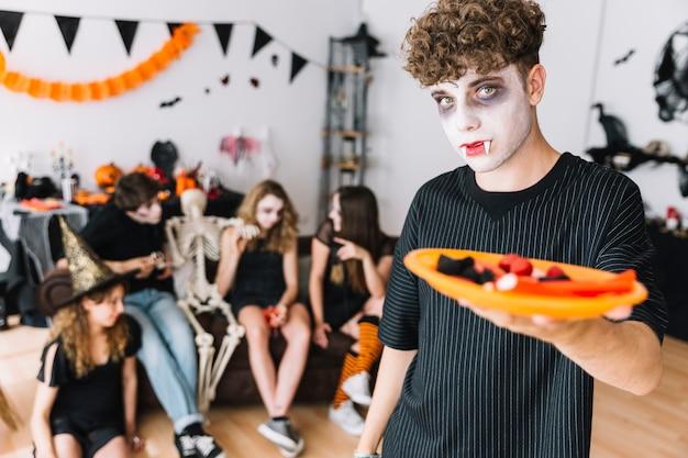 Adolescente con le zanne e vampiro torvo dando piatto con caramelle