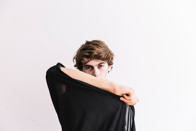 Teenage boy with halloween grim and black cloak