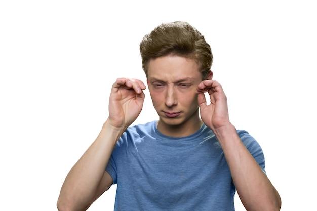 Подросток с головной болью, изолированные на белой стене. подчеркнул усталый подросток мужского пола.