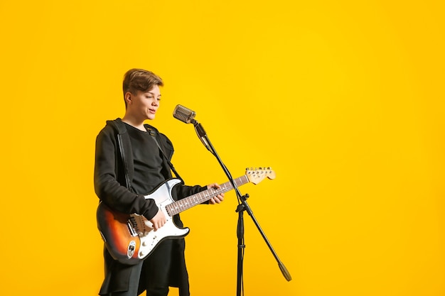 Teenage boy with microphone singing and playing guitar against color