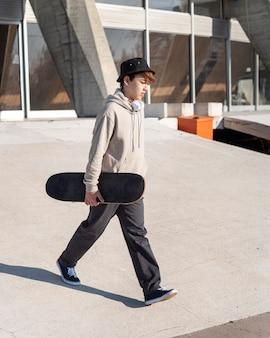 スケートボードを持つ10代の少年