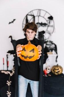 Teenage boy with zombie grim holding pumpkin in hands