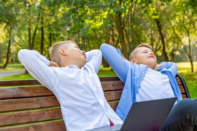 Teenage boys on park bench развлекаются и отдыхают