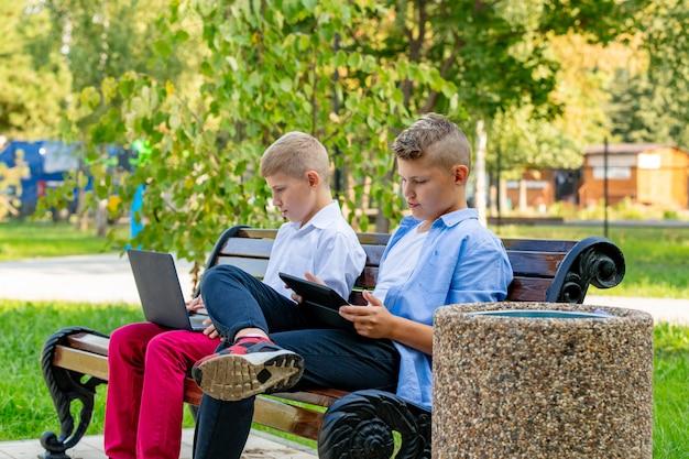 Подростки на скамейке в парке, используя ноутбук и цифровой планшет
