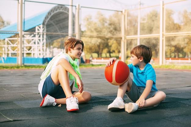 10代の少年はバスケットボールコートに座って、トレーニングの後にリラックスします。