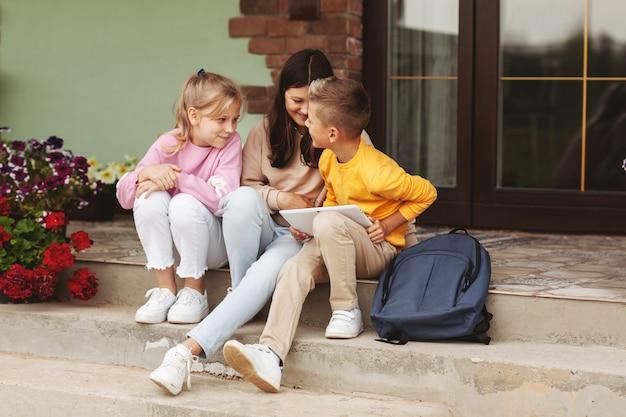 Дети-подростки после школы сидят на ступеньках и играют на цифровом планшете