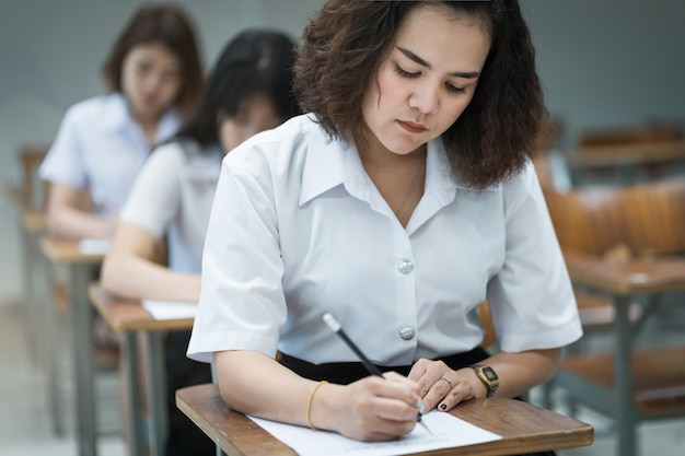 Teenage college students write on examination paper answer sheet in the classroom
