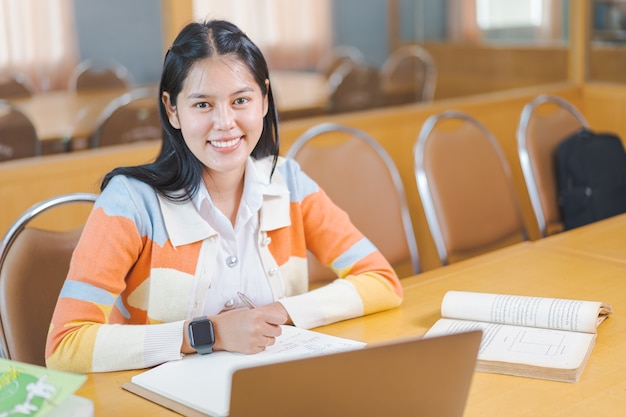 10代の大学生が教室で試験紙の解答用紙に書く