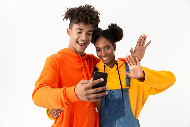 Пара подростков в красочной одежде, делающая селфи фото на мобильный телефон, изолированные на белой стене