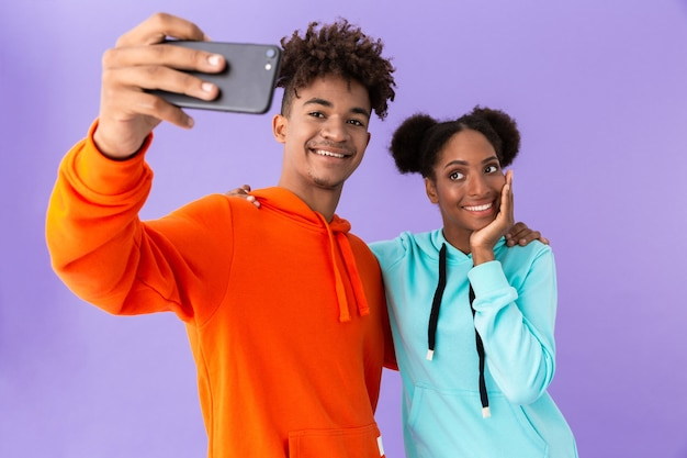 Teenage couple wearing colorful sweatshirts taking selfie on smartphone, isolated over violet wall