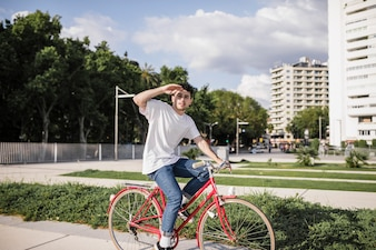 Teenage cyclist riding bike and shielding eyes