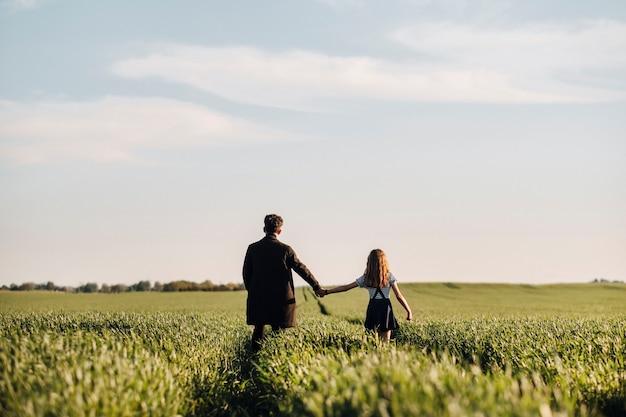 10代の娘は、夕方に手をつないで牧草地で父親と一緒に歩きます。