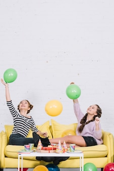 Teenage female friends sitting on sofa playing with balloons in the birthday party