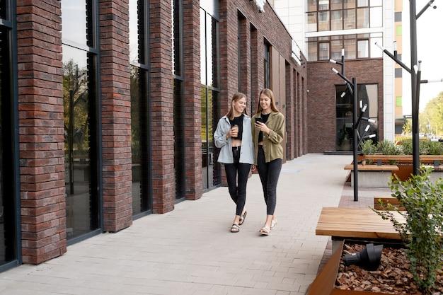 도시 환경에서 길을 따라 이동하는 십대 여성 쌍둥이