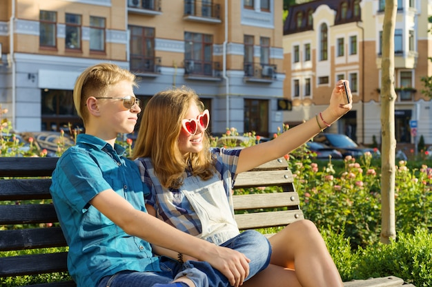 Teenage friends girl and boy sitting on bench in city, talking