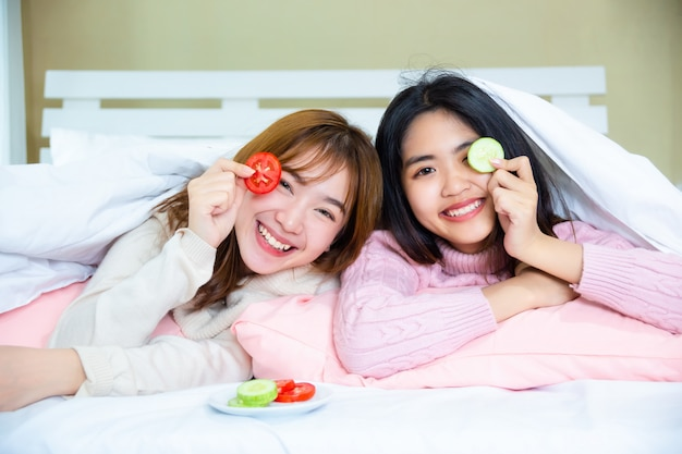 Teenage friends lying under blanket with pillows on bed