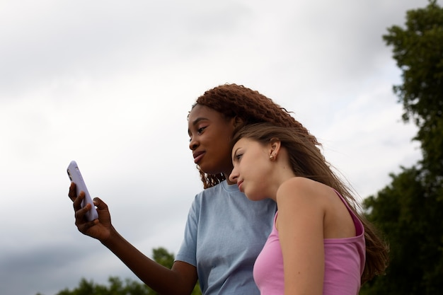 Teenage friends using smartphone outdoors