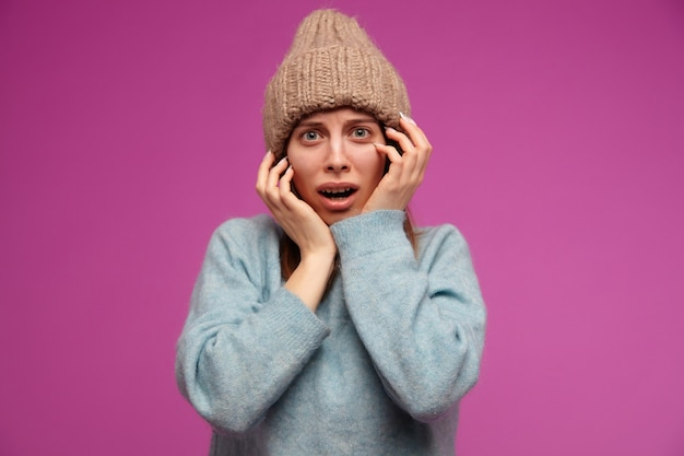 십 대 소녀, 갈색 머리 긴 머리를 가진 두려워 보는 여자. 파란색 스웨터와 니트 모자를 착용. 보라색 벽 너머 공포로 그녀의 얼굴을 만져