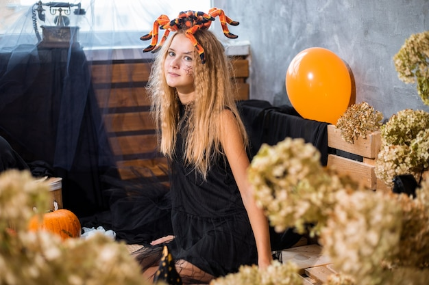 할로윈 휴가를 위한 장식용 마른 꽃들 사이에서 10대 소녀, 그녀의 머리에 거대한 거미. 클로즈업 사진, 오렌지 블랙 색상