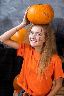 할로윈 휴가를 위한 장식 중 10대 소녀, 머리에 거대한 호박