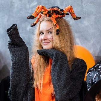 할로윈 휴가를 위한 장식 중 10대 소녀, 그녀의 머리에 거대한 거미. 사진, 주황색 bakc 색상을 닫습니다.