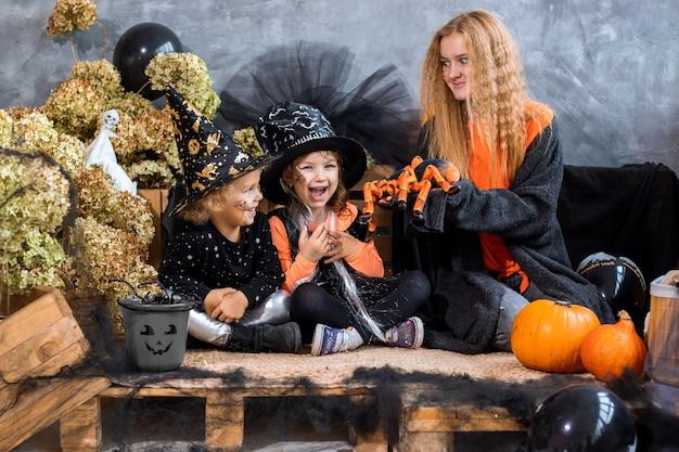 4-5세 두 자매와 함께 할로윈 휴가를 위한 장식 중 10대 소녀는 검은색과 주황색 장식, 유머 사진 배경에서 즐거운 시간을 보냅니다.