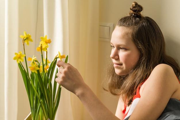 10代の少女と黄色の春の花の花束