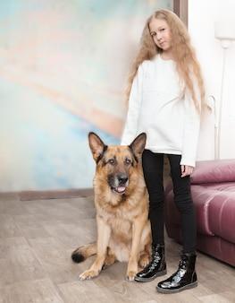 10代の少女と彼女のフレンドリーな大きな犬が居間に立っています Premium写真