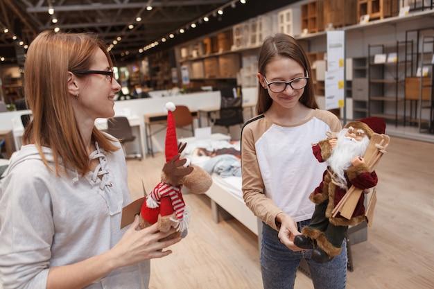 Девочка-подросток и ее мать вместе покупают рождественские украшения в магазине товаров для дома