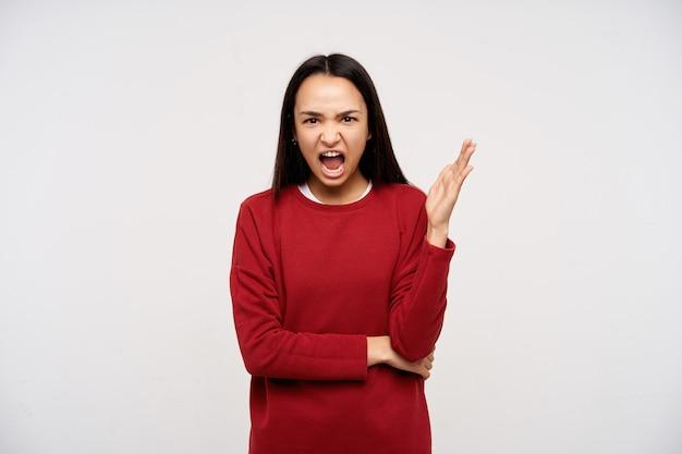 10代の少女、暗い長い髪の怒っているアジアの女性。赤いセーターを着て、持ち上げた手で怒りを叫ぶ。白い背景の上に隔離されたカメラを見て、イライラして叫ぶ