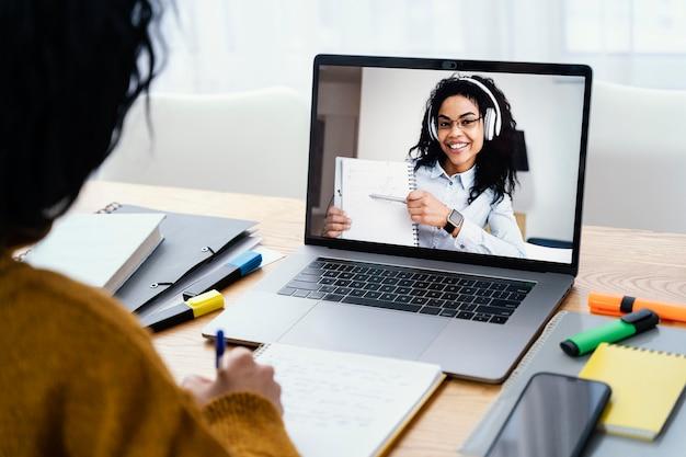 ノートパソコンでオンライン学校の間に自宅で10代の少女