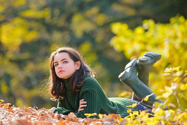 Teenage girl in autumn foliage, beauty portrait. young teen in a romantic autumn scenery.