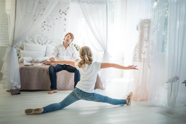 ベッドに座っている疲れた父親の前の床に10代の少女バレリーナが絡まる