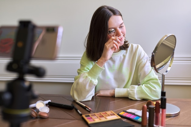 Teenage girl, beauty blogger filming video for channel blog, showing eyelash curler. telling and showing makeup and does invisible natural makeup. beauty, technology, communication teenagers online