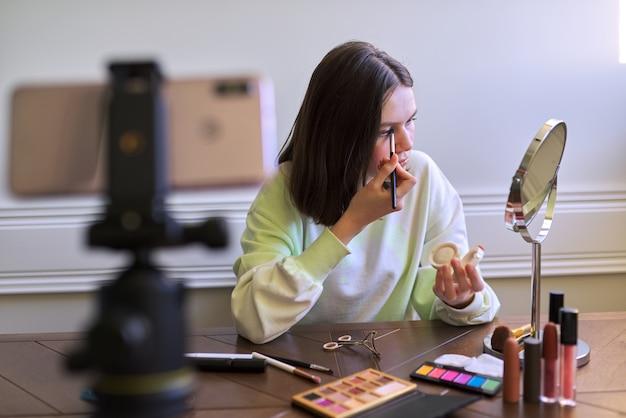 Девушка-подросток, бьюти-блогер снимает видео для блога канала, раскрашивает тени. рассказывает и показывает макияж и делает невидимый естественный макияж. красота, технологии, общение подростков онлайн