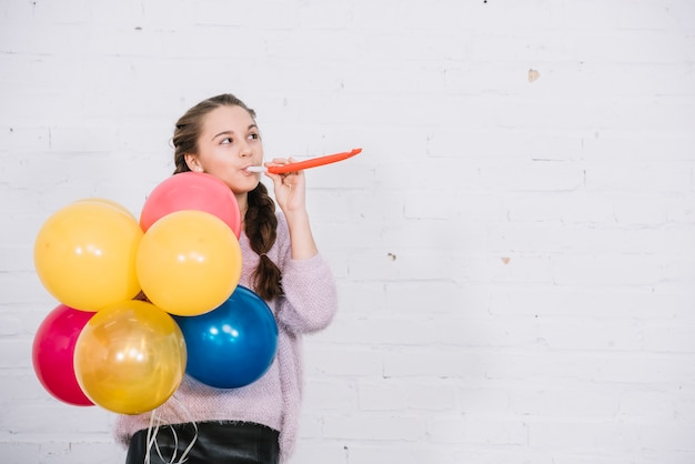 Teenage girl blowing party horn holding colorful balloons in hand