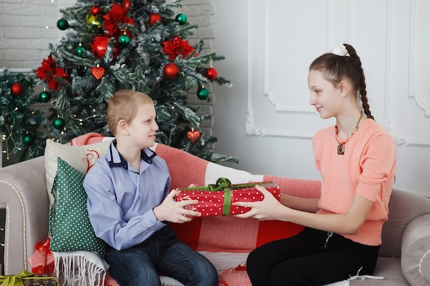 Teenage girl and boy near christmas tree give gift boxes while sitting on a bench.