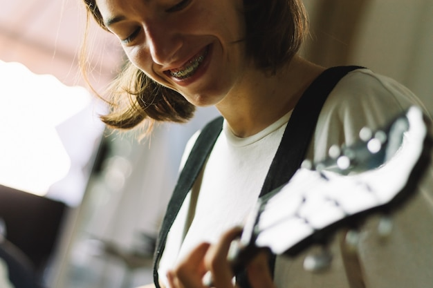 Teenage girl in braces learning to play guitar with a smile. concept of smiling while learning.