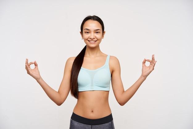 10代の少女、暗い長い髪の穏やかなアジアの女性。スポーツウェアを着て瞑想し、穏やかな笑顔でリラックスしてください。白い背景の上に分離されたカメラで見て