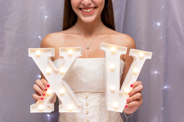Teenage girl celebrating quinceañera while holding roman numerals