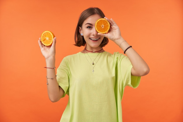 10代の少女は、オレンジを目の上に持っている短いブルネットの髪で陽気で幸せで、片目を覆っています。オレンジ色の壁の上に立っています。緑のtシャツ、歯列矯正器、ブレスレットを着用